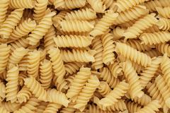 close-up of dry uncooked rotini texture background - stock photo
