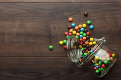 Overturned glass jar full of colorful sweets Stock Photos