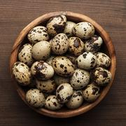 quail eggs on the brown wooden table - stock photo