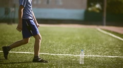Boy teenager  tired football  athlete drinks water from a plastic bottle sits on Stock Footage