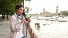 Mixed race woman relaxing and listening music in London on a cloudy day Stock Footage
