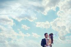 Just married bride and groom with baloons in hand over cloudy sky Stock Photos