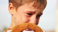 Dirty orphan boy close-up crying and petting a stuffed toy wipes the tears on Stock Footage