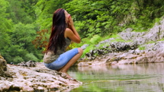 Young woman washing face and refreshes in a mountain river Stock Footage