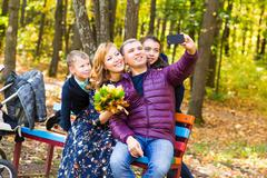 family, childhood, season, technology and people concept - happy family taking - stock photo