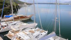 Luxury Catamarans boats and yachts anchored at the marina port - aerial Stock Footage