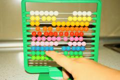 One little child learns math on abacus Stock Photos