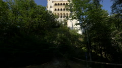 View of the Neuschwanstein Castle from an alley in the forest Stock Footage