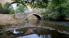 Old stone bridge over river La Cure in the Pierre-Perthuis, Burgundy, France Stock Footage