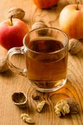 tea with apples and nuts on wooden table - stock photo