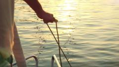 Sailor hands pull the rope to pull the anchor in slowmotion and set sail at Stock Footage
