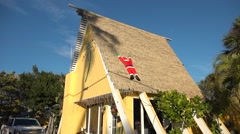 Santa flattened on the thatch roof of a tiki themed A frame marks Christmas in Stock Footage