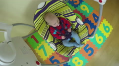 Infant baby boy or girl sway in colorful swing at home. 4K Stock Footage