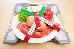 Low-carbohydrate diet food on a scale - stock photo