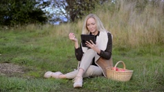 Young woman holding in one hand apple, in the other hand tablet - stock footage
