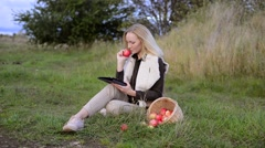 Young woman eats fresh apple outdoor and wathing movie on tablet Stock Footage