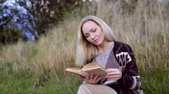 Young woman lying. reading book and wathing at camera - stock footage