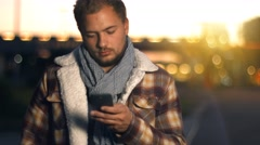 Handsome young man sms texting using app on smart phone at autumn night in city Stock Footage