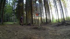 Disc golf players putting at a basket surrounded by forest Stock Footage
