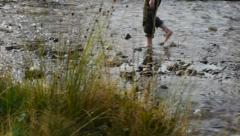 Fugitive walk barefoot through a mountain river with little water 47a Stock Footage
