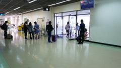 Exit to gate 14, old int airport, chinese passengers come through doorway Stock Footage