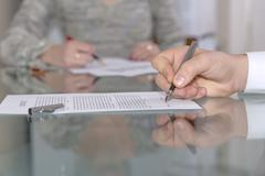 Male hand signing formal paper Stock Photos
