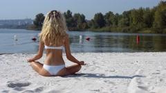 Girl in white bikini in lotus position on beach sand Stock Footage