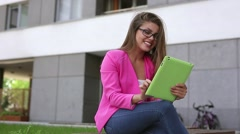 Young beautiful businesswoman sitting on a bench with green tablet. Stock Footage