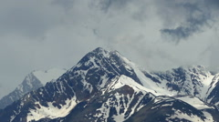 snow-capped mountain peaks among the clouds - stock footage
