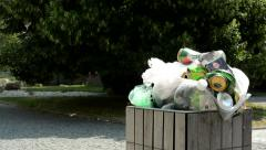 Camera focus overfilled trash can with garbage in the park near by building Stock Footage