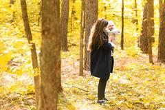 Happy young mother with little daughter in autumn park - stock photo