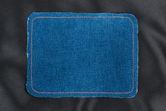 Frame made of denim fabric with yellow stitching on black silk Stock Photos