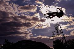 Mountain biker jumps through the air - stock photo