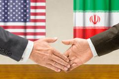 Representatives of the USA and Iran shake hands Stock Photos