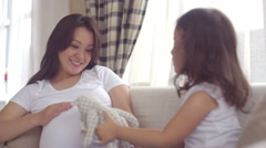 The daughter plays the mother of a pregnant belly, Dolly shot, close-up Stock Footage