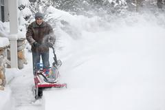 Man clearing driveway with snowblower - stock photo