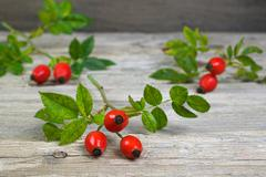 Rosehips on an old wooden table, nature, red Stock Photos