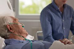 Relative visits elderly hospitalized man - stock photo