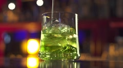 Coctail poured into glass on bar table Stock Footage