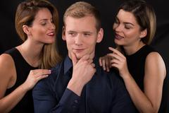 Alluring women seducing narcissistic man - stock photo