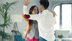 Young, happy couple dancing at home Stock Footage