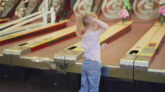 A little girl tries throwing a skee ball Stock Footage