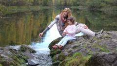 A young mother and her daughter sitting on the Bank of a forest lake. Stock Footage