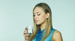 Attractive blonde drinking water from a glass on a white background Stock Footage