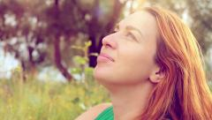 Romantic red-haired young woman in green smiles dress and lays down on a flower Stock Footage