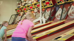 A young girl helps another little girl learn how to play skee ball Stock Footage