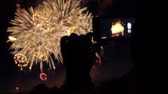 Taking video with smartphone during colorful fireworks in the night sky - stock footage