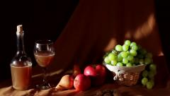 Fruit basket with grapes, pears, glass, organic wine bottle and nuts Stock Footage