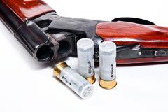 Hunting shotgun and ammunition on white background. Stock Photos