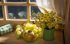 Stock Photo of bouquet of wild flowers with grapes and an apple near a window